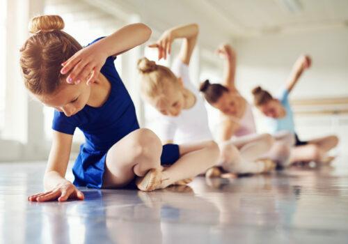 Little,Ballerinas,Doing,Exercises,And,Bending,Sitting,On,Floor,In